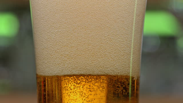 slo mo ld bubbles settling after beer is being poured into a glass - beer glass stock videos & royalty-free footage