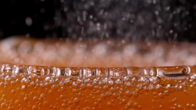 bubbling orange soda drink fizzing in glass - close up - carbonated drink stock videos & royalty-free footage