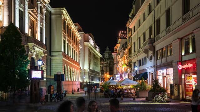 timelapse bucarest di notte quartiere storico con traffico e pedestiani - romania video stock e b–roll