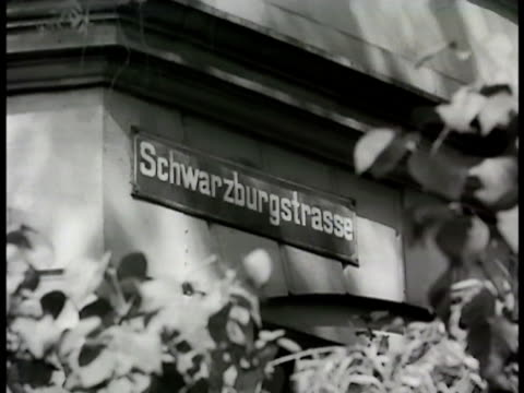 vídeos de stock, filmes e b-roll de ext 'buchner' home w/ bombed building bg cu street sign schwarzburgstrasse int 'buchner' home w/ family sitting in dining room 'mr buchner' adjusting... - 1948