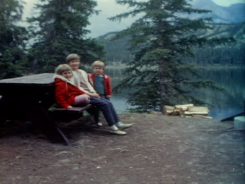 vidéos et rushes de a buck deer walks away and children get up off a bench and walk towards a pond. - frère
