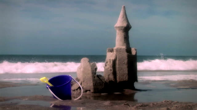 a bucket and shovel rest in the sand near a sand castle on a beach. - eimer stock-videos und b-roll-filmmaterial