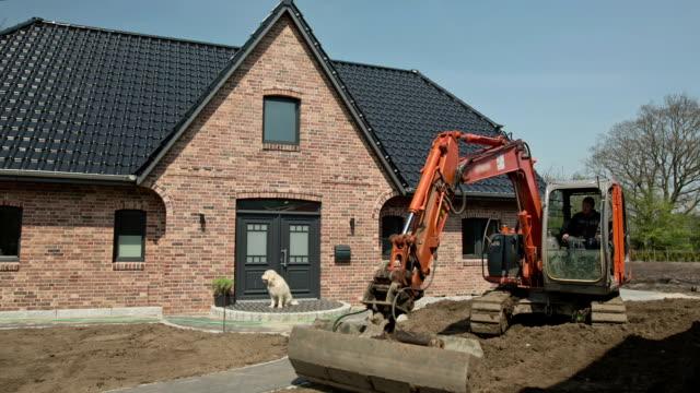 vídeos de stock, filmes e b-roll de a bucket digger leveled the garden soil of a new family home. - facade