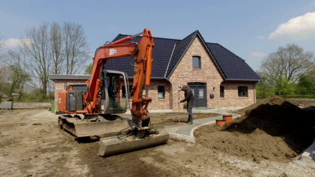 a bucket digger leveled the garden soil of a new family home. - construction vehicle stock videos and b-roll footage