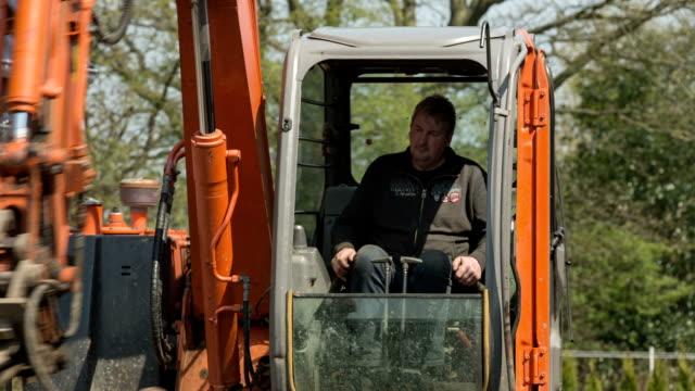 vidéos et rushes de a bucket digger leveled the garden soil of a new family home. - pelleteuse