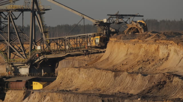 vidéos et rushes de a bucket excavator removes top layers of earth in order to reach the lignite coal lying underneath at the jaenschwalde openpit coal mine on january... - enlever