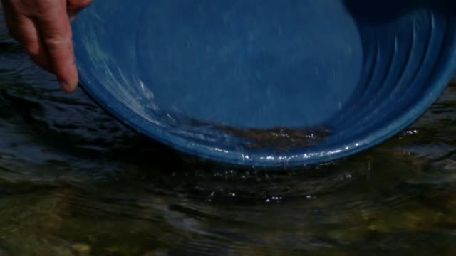 bucket is swirled during gold panning process in zubiena, italy - panning stock videos & royalty-free footage