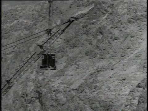 vídeos de stock, filmes e b-roll de bucket lifting / bucket swinging across canyon / bucket lowering to workers waiting by forms - represa hoover
