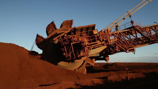 vídeos de stock e filmes b-roll de a bucket wheel reclaimer collects iron ore from a stockpile at fortescue metals group ltd's herb elliott port facility in port hedland australia on... - balde