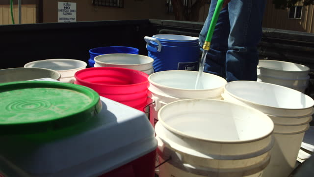 vídeos de stock e filmes b-roll de buckets of water being filled during contamination problem in new mexico - balde