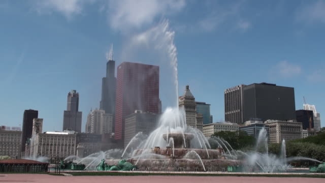 buckingham fountain with chicago skyline in background - buckingham fountain stock videos & royalty-free footage