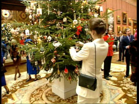 Christmas tree EEN NICHOLAS OWEN ENGLAND London Buckingham Palace Int GV Decorated Christmas tree TILT UP Queen Elizabeth II putting decoration on...