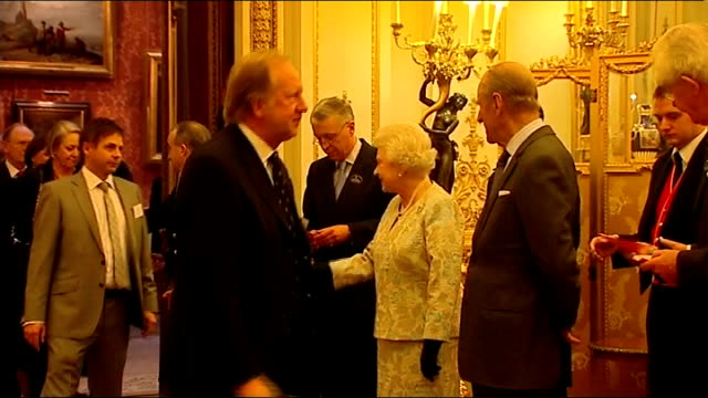 buckingham palace hosts reception for the british clothing industry int queen elizabeth ii and prince philip shaking hands with harold tillman and... - milliner stock videos and b-roll footage
