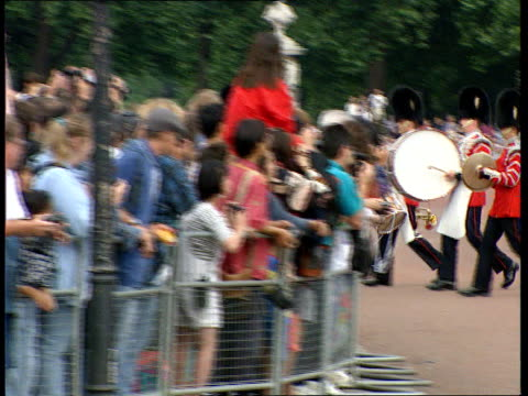 stockvideo's en b-roll-footage met buckingham palace opens to public:; england: london: buckingham palace: lms band marching along to palace r-l many tourists standing outside - itv evening bulletin