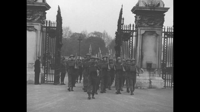 gv buckingham palace / victoria memorial military band marches / home guard soldiers march through palace gate carrying rifles / various shots crowds... - home guard britannica video stock e b–roll
