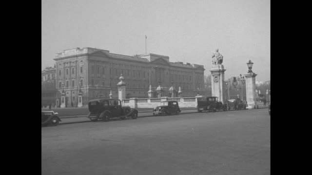 buckingham palace with parked cars / people gathered outside the gate of the palace / king's guard on sidewalk between fence and people / note exact... - abdication stock videos and b-roll footage