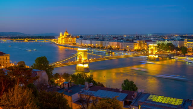 budapest city skyline with hungarian parliament and chain bridge at danube river, day to night timelapse, budapest, hungary - chain bridge suspension bridge stock videos & royalty-free footage