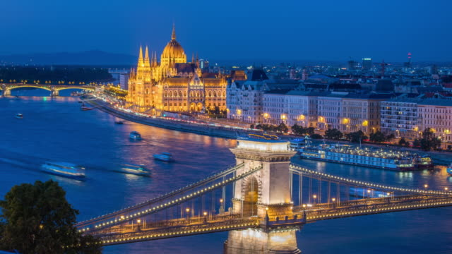 vídeos de stock e filmes b-roll de budapest city skyline with hungarian parliament and chain bridge at danube river, day to night timelapse, budapest, hungary - ponte széchenyi lánchíd