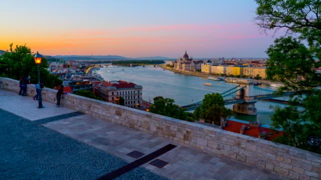 vídeos de stock e filmes b-roll de budapest city skyline with hungarian parliament and chain bridge at danube river, day to night timelapse, budapest, hungary - ponte das correntes ponte suspensa