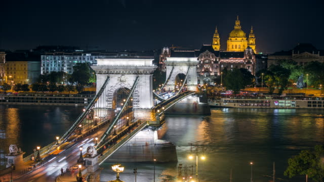 vídeos de stock e filmes b-roll de budapest city skyline with st. stephen's basilica and chain bridge at danube river, day to night time lapse, budapest, hungary - ponte das correntes ponte suspensa