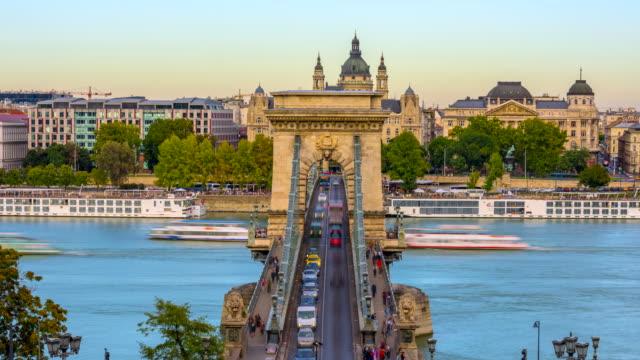 vídeos de stock e filmes b-roll de budapest city skyline with st. stephen's basilica and chain bridge at danube river, day to night time lapse, budapest, hungary - ponte das correntes ponte suspensa