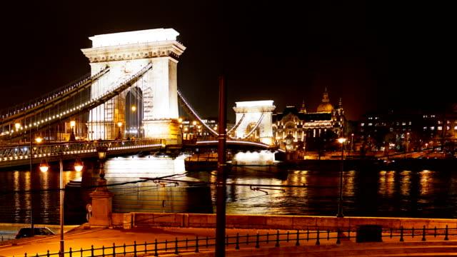 stockvideo's en b-roll-footage met de stadshemy skyline van boedapest met st. stephen's basilica en kettingbrug bij rivier donau, dag aan nachttijdval, boedapest, hongarije - chain bridge suspension bridge