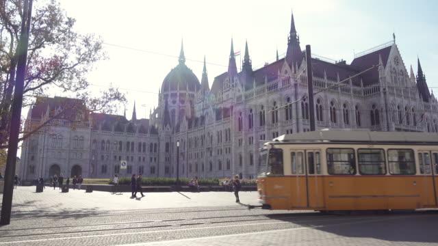 budapest parliament of hungary with tram - osteuropäische kultur stock-videos und b-roll-filmmaterial