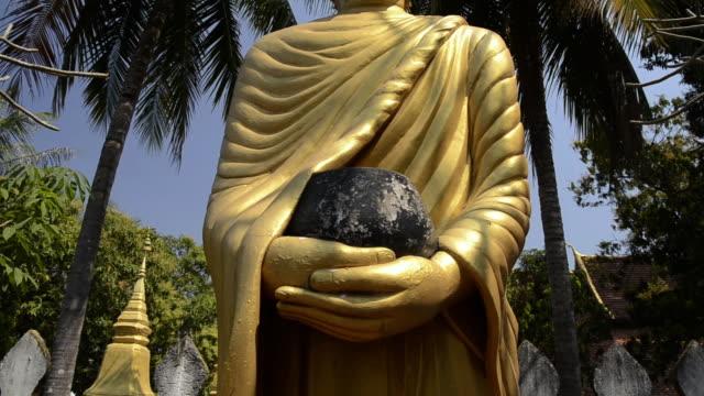 MS TU Buddha figure with alms bowl under palm tree  AUDIO / Luang Prabang, Luang Prabang, Laos