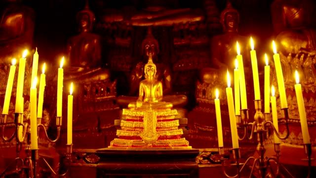buddha-statue im tempel mit kerze in der nacht.4k zeitlupe. - buddhismus stock-videos und b-roll-filmmaterial