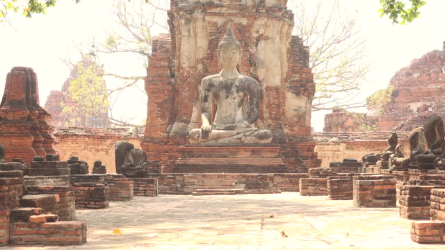 buddha statue sitting in meditation in the ruins of wat mahathat in ayutthaya, thailand - 遺跡点の映像素材/bロール