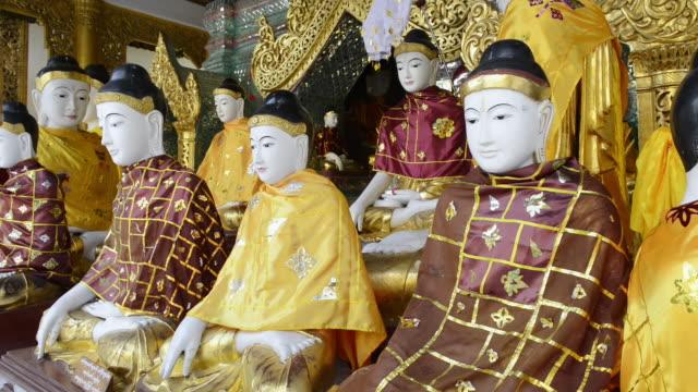 MS Buddha statues wearing colorful robes in shwedagon pagoda / Yangon, Yangon Division, Myanmar