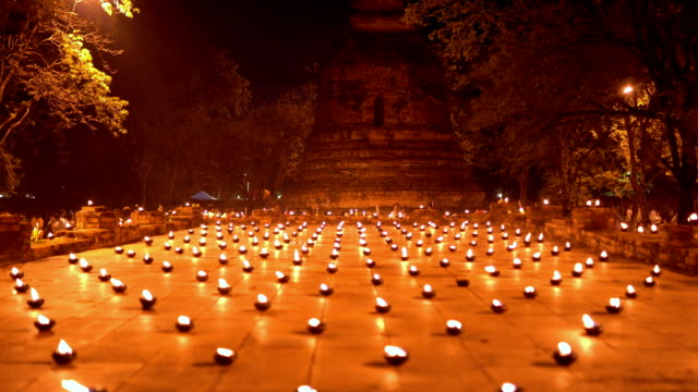 buddhism lighted candles trail around ancient temple - buddha stock videos & royalty-free footage