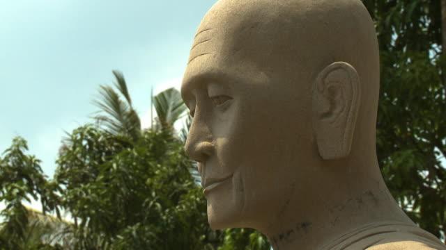 buddhist bald head sculpture in san tok, cambodia - effigy stock videos & royalty-free footage