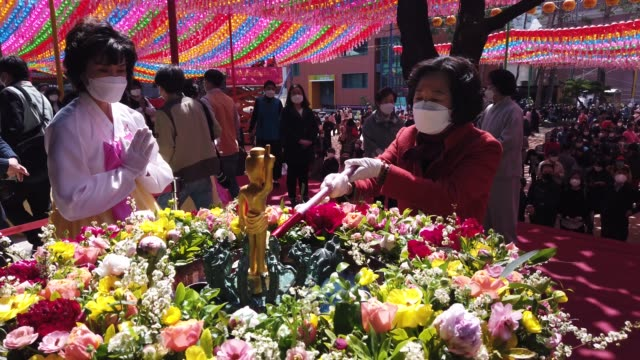 buddhist believer wears a mask as a preventive measure against the coronavirus pours water on a small statue of buddha during a birthday of buddha... - coreano video stock e b–roll