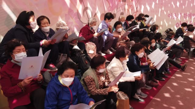 stockvideo's en b-roll-footage met buddhist believers wear masks as a preventive measure against the coronavirus attend a birthday of buddha and service to pray for overcoming the... - gelovige