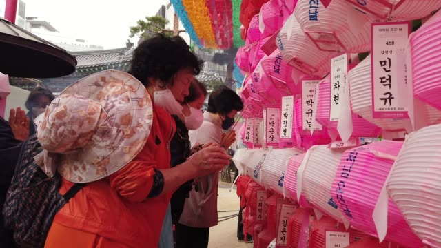 buddhist believers wear masks as a preventive measure against the coronavirus attend a birthday of buddha and service to pray for overcoming the... - coreano video stock e b–roll