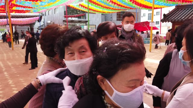 buddhist believers wear masks as a preventive measure against the coronavirus receive body temperature check as they arrive to attend a birthday of... - coreano video stock e b–roll