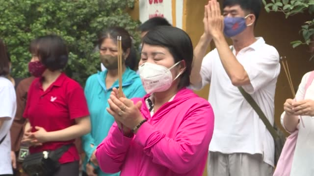 buddhist devotees in vietnam wear face masks and pray at pagodas to celebrate vesak day which also marks buddha's birthday - pagoda stock videos & royalty-free footage