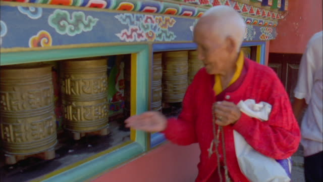 a buddhist man clutches his prayer beads as he spins prayer wheels. available in hd. - prayer beads stock videos & royalty-free footage