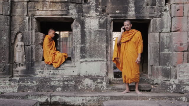 ws a buddhist monk attempts to meditate while another makes a call on a mobile phone at an ancient temple in angkor wat / siem reap, cambodia - robe stock videos & royalty-free footage