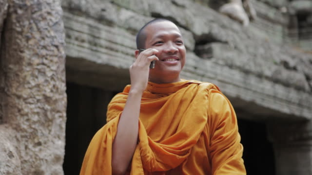 cu a buddhist monk makes a call on a mobile phone and talks, laughing and smiling, next to an old tree and ancient temple in angkor wat / siem reap, cambodia - orange stock videos & royalty-free footage
