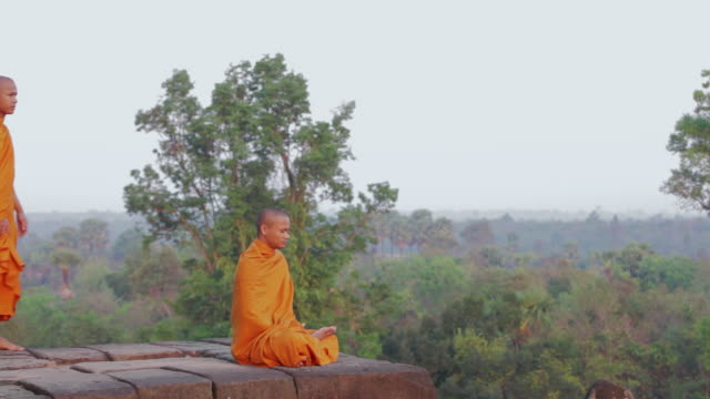 WS A Buddhist monk meditates and is joined by another who stands looking out at the sun rising above the jungle on an ancient temple in Angkor Wat / Siem Reap, Cambodia