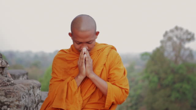 cu a buddhist monk performs a sampeah or traditional cambodian greeting, similar to a wai in thailand, on an ancient temple in angkor wat / siem reap, cambodia - respect点の映像素材/bロール