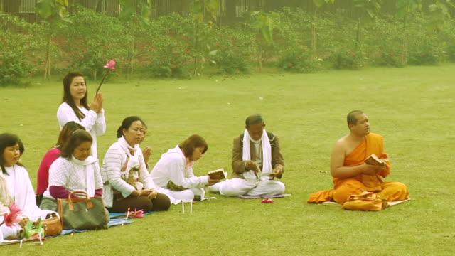 MS Buddhist monk praying with devotees in lawn / Sarnath, Uttar Pradesh, India