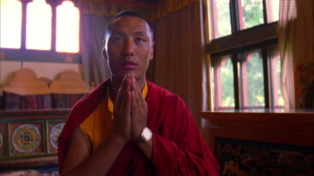 A Buddhist monk prays in a house. Available in HD.
