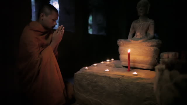 vídeos de stock e filmes b-roll de ms, tu a buddhist monk prays to a buddha statue lit by candles in an ancient temple in angkor wat / siem reap, cambodia - buda