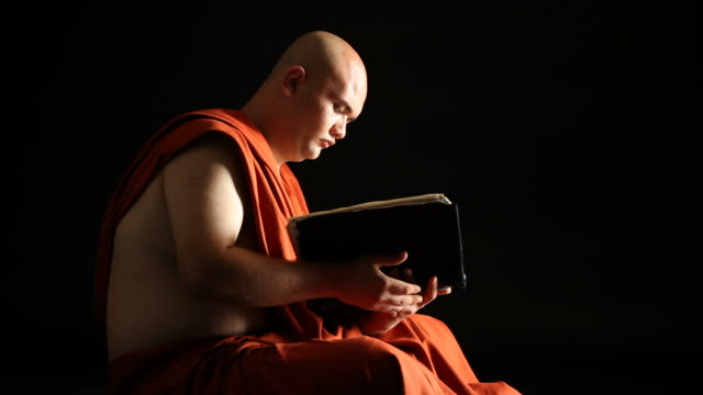 stockvideo's en b-roll-footage met buddhist monk reading holy book in dark - selimaksan