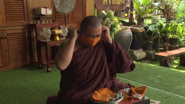 "buddhist monk scrawls a prayer on an orange face mask beseeching ""an end to the suffering"" caused by the deadly coronavirus -- a finishing touch to... - buddhism video stock e b–roll"