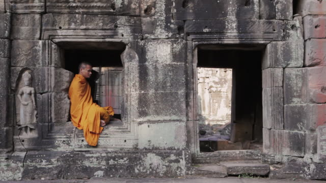 WS A Buddhist monk sits meditating while other monks walk past in an ancient temple in Angkor Wat / Siem Reap, Cambodia