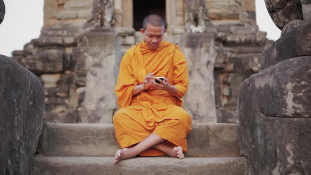 ws, pan a buddhist monk taps on the screen of a smartphone on an ancient temple in angkor wat / siem reap, cambodia - contrasts stock videos & royalty-free footage